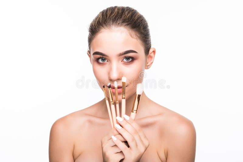 Portrait of young pretty woman hiding face behind makeup brushes isolated on white. Skin care, cosmetology concept. stock photography
