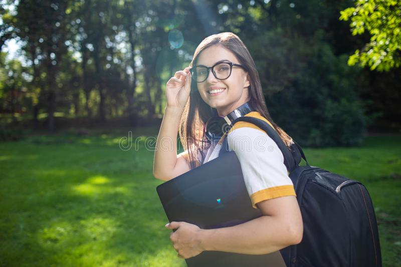 Young Pretty Woman with Laptop and Daypack royalty free stock image