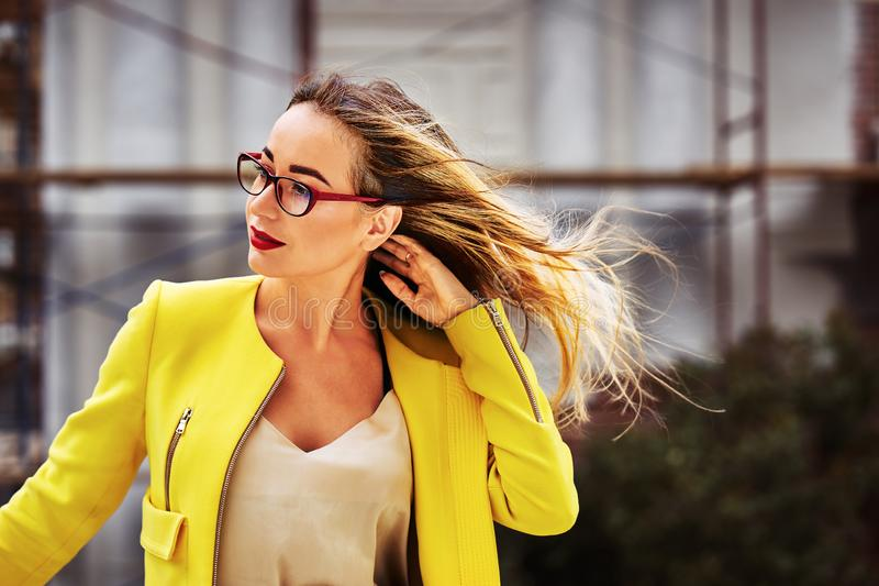 Portrait of a young pretty woman with long hair wearing glasses and a yellow jacket royalty free stock image