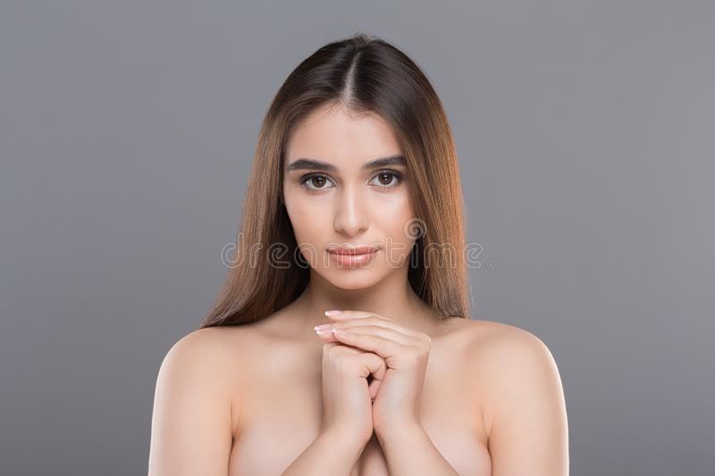 Portrait of young pretty woman perfect smooth skin. Pure beauty. Portrait of young pretty woman perfect smooth skin, posing with bare shoulders, grey studio stock photography