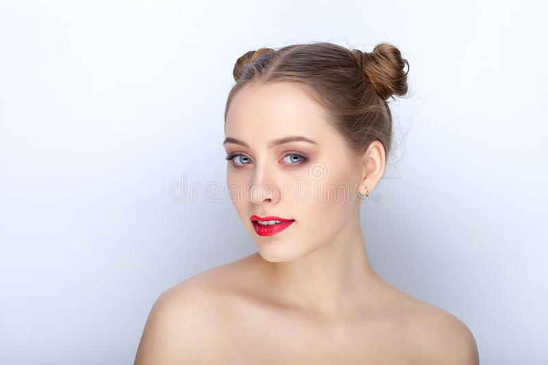 Portrait of a young pretty woman with trendy makeup bright red lips funny bun hairstyle and bare shoulders act the ape against. Portrait of a young pretty lady royalty free stock images
