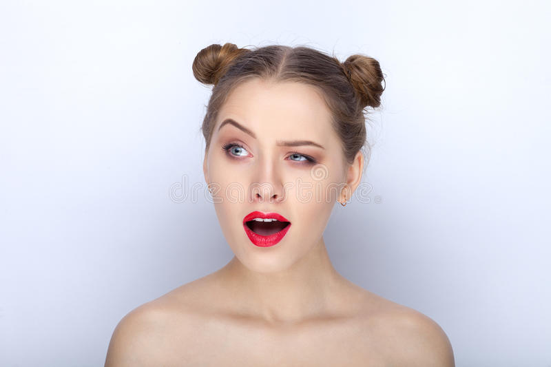 Portrait of a young pretty woman with trendy makeup bright red lips funny bun hairstyle and bare shoulders act the ape against. Portrait of a young pretty lady royalty free stock photos