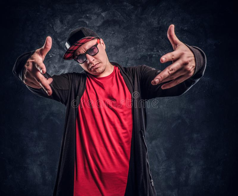 Portrait of a young rapper dressed in a hip-hop style, posing for a camera. Studio photo against a dark wall royalty free stock image