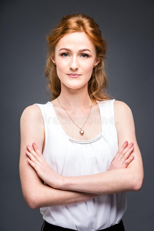 Portrait of a young redhaired beautiful girl in the studio on a gray isolated background. A woman is standing with her arms folded. Portrait of a young red stock image