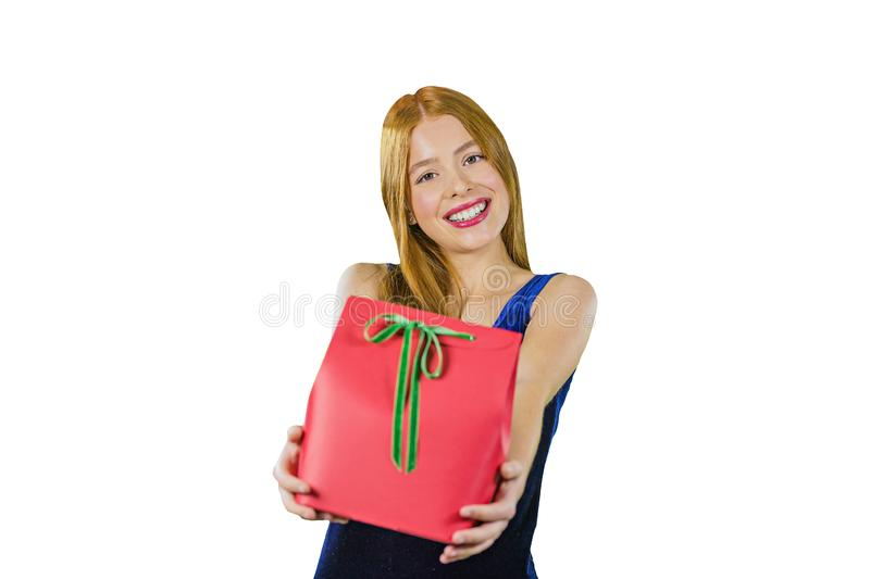 Portrait of a young red-haired girl in a blue evening dress with a gift in hand, holding a gift on her outstretched arms royalty free stock photography