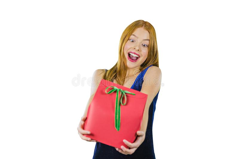 A portrait of a young red-haired girl in a blue evening dress with a gift in her hands, holding a gift on outstretched stock photography
