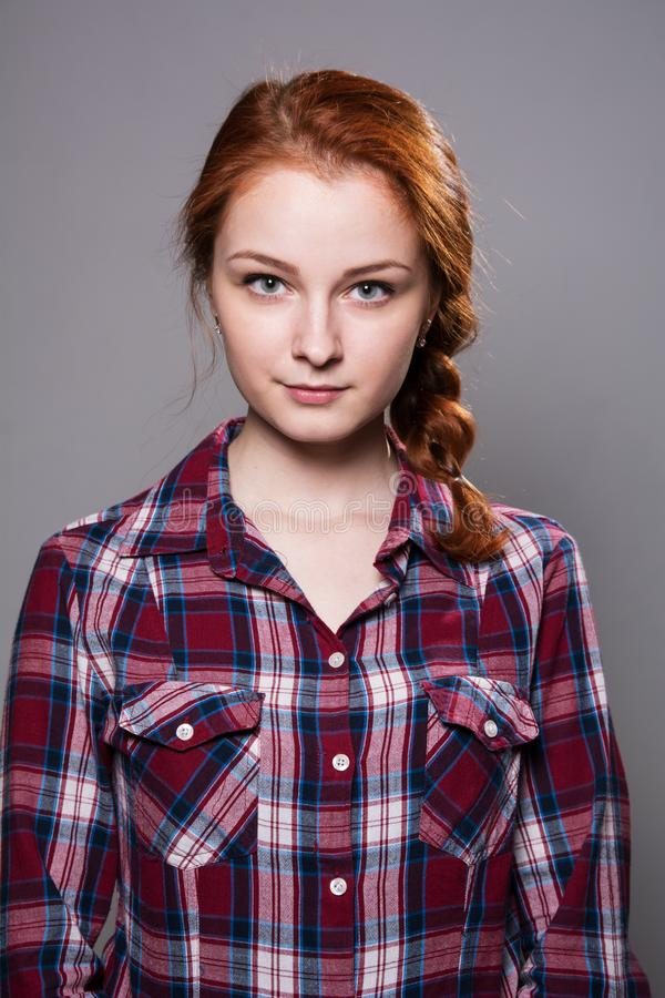 Portrait of a young red-haired girl in a plaid shirt on a gray background stock photos