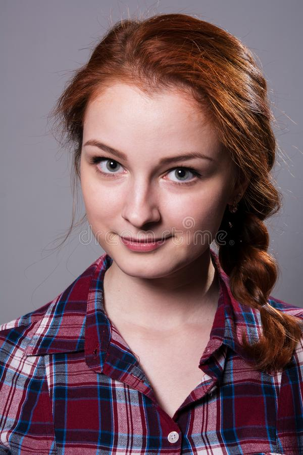 Portrait of a young red-haired girl in a plaid shirt royalty free stock photo