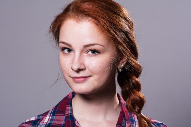 Portrait of a young red-haired girl in a plaid shirt royalty free stock photography