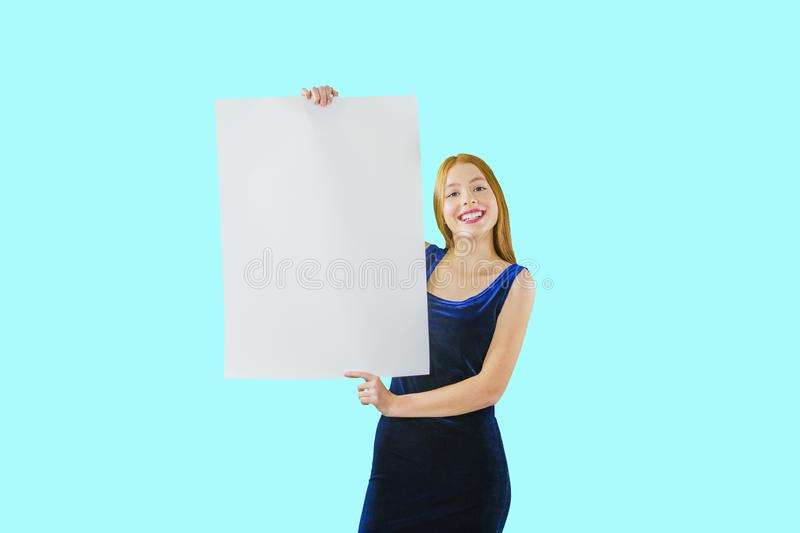 Portrait of a young red-haired girl who holds both hands along the length of the poster looking at the camera and stock photo