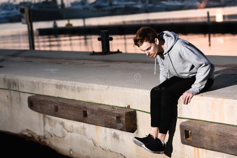 Portrait of young red-haired man with gray sweatshirt sitting on the jetty of a harbor at sunset.  royalty free stock image