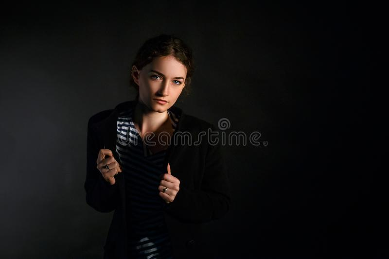 Portrait of a young red-haired woman in a coat on a black background stock photography