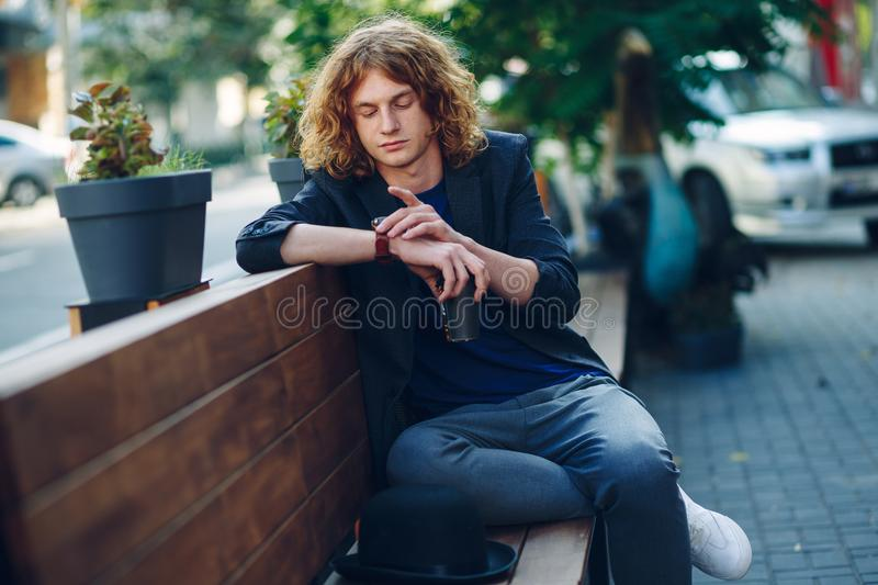 Red haired hipster man sitting on bench looking to his watch royalty free stock images