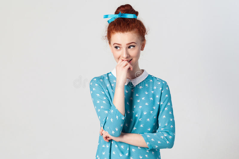 Portrait of young redhead female model having shy cute smile, holding hand on her lips, posing indoors. royalty free stock photos