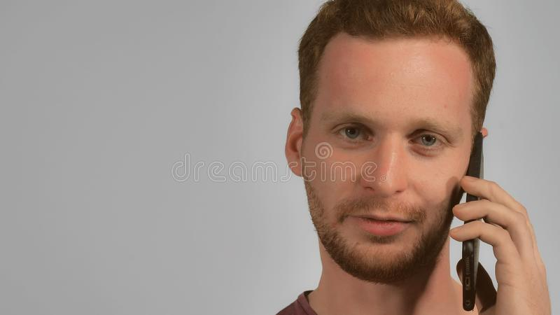 Caucasian male talking by cellular stock photo
