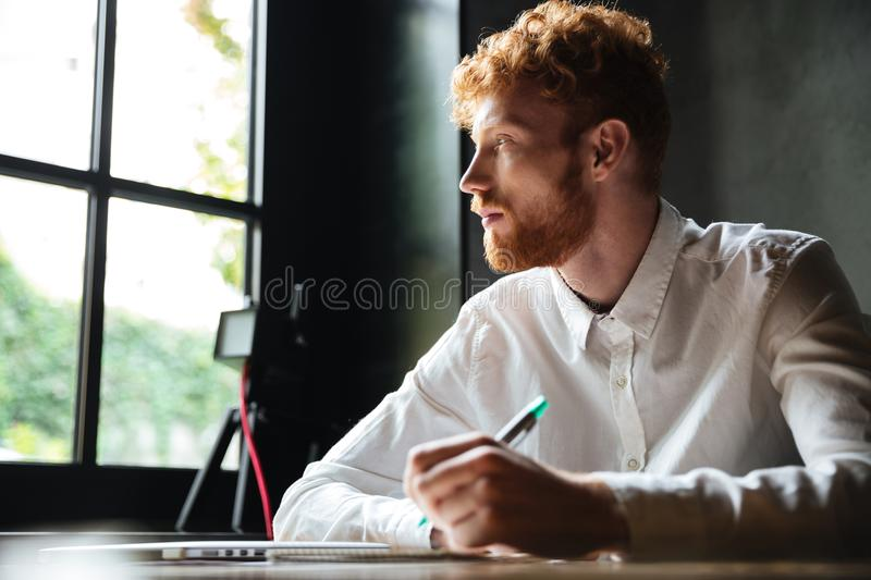 Portrait of a young redhead man writing in a notebook. And looking at a window while sitting indoors royalty free stock photography