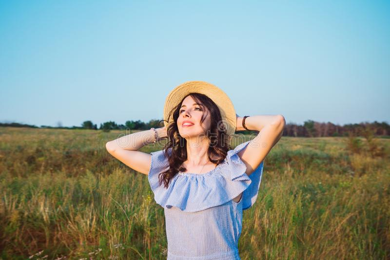 Portrait of young relaxed caucasian woman in blue romantic dress and straw hat on green meadow enjoying summer sunset. Calm and stock photo