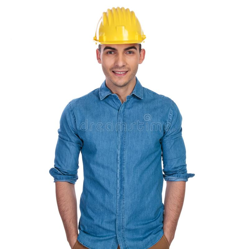 Portrait of young and relaxed engineer student wearing yellow helmet stock image