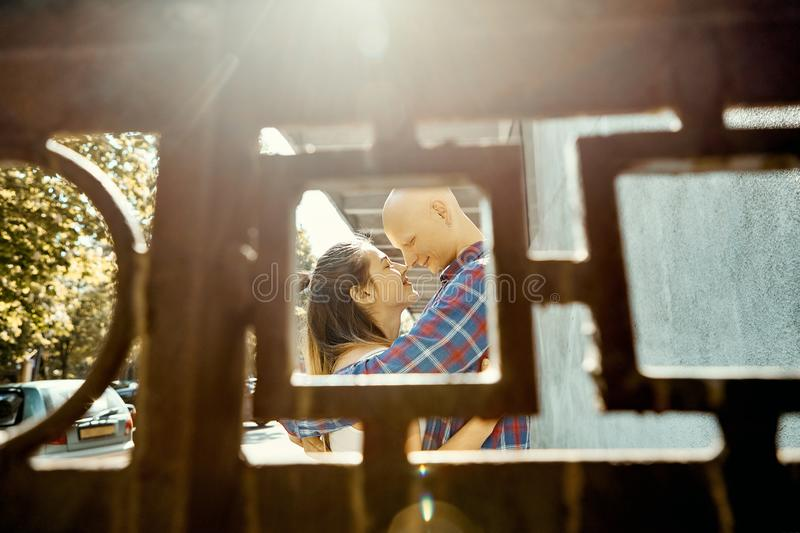 Portrait of young romantic couple in love spend time in the park. Young man tenderly embracing young woman, view through royalty free stock photo