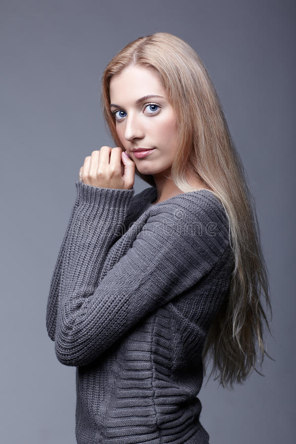 Portrait of young romantic woman in gray woolen sweater. Beautiful girl posing on grey studio background. Female with blonde hair royalty free stock photo