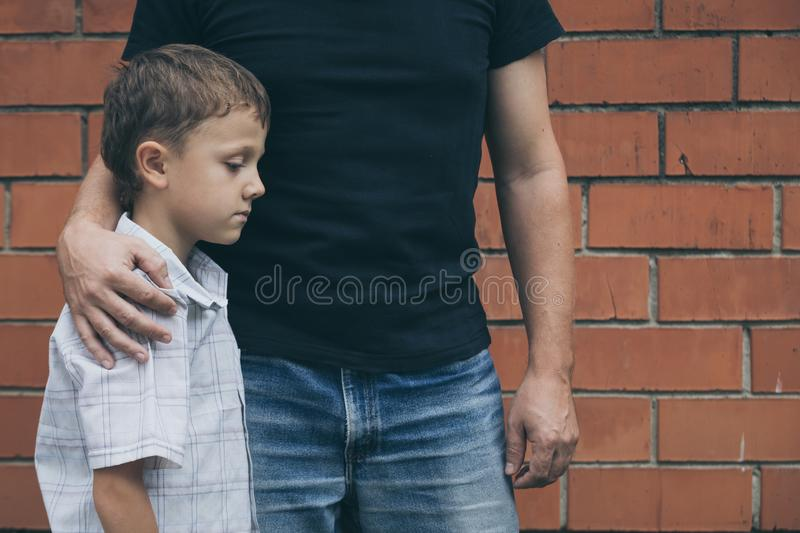 Portrait of young sad little boy and father sitting outdoors at stock photos