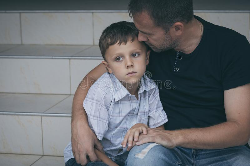 Portrait of young sad little boy and father sitting outdoors at royalty free stock photos