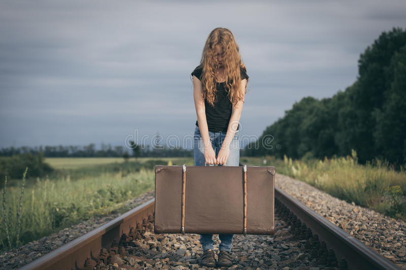 Portrait of young sad ten girl standing with suitcase outdoors a. Portrait of young sad ten girl standing with suitcase outdoors on the railway at the day time stock photos