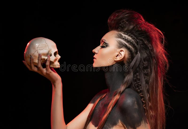 Portrait of a young savage girl who holds a skull in her hand. Naked shoulders and neck are covered with black paint. Conceptual stock photos