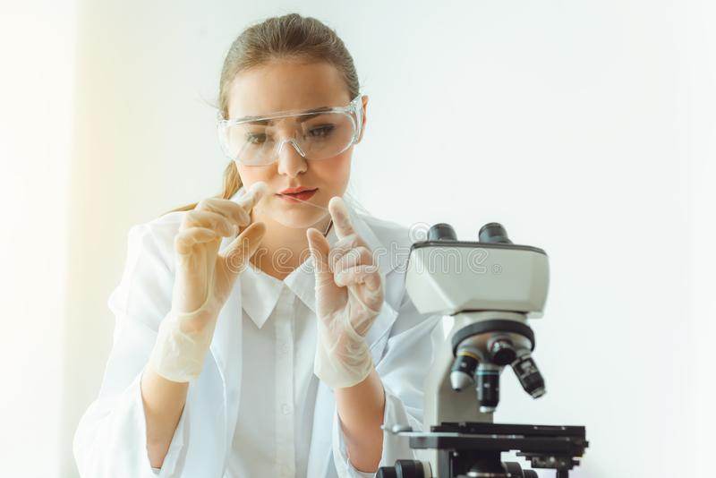 Portrait of young scientist research is looking at the microscope slide in the laboratory room, Biotechnology, Science, Chemistry stock images