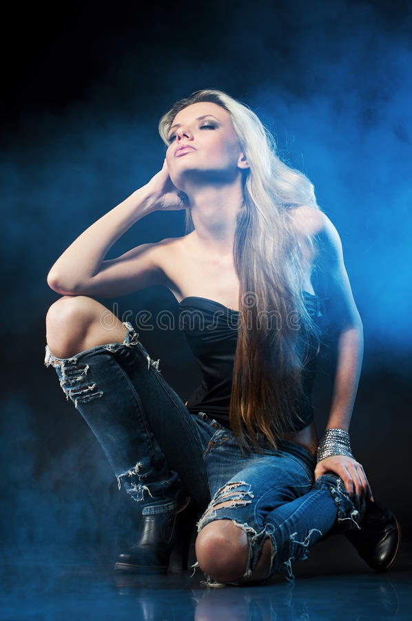 Portrait of young seductive woman. In the blue smoke royalty free stock image