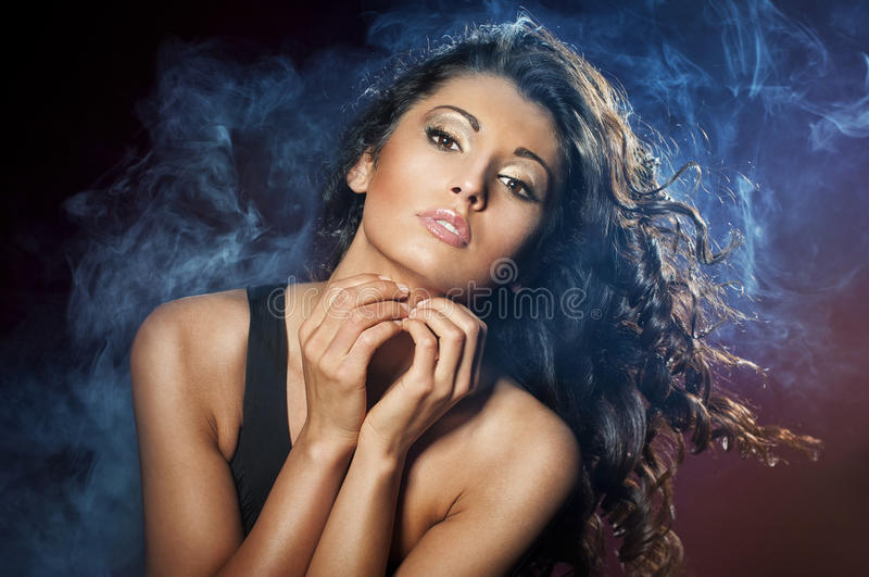 Portrait of young seductive woman. In the blue smoke on the black background stock photos