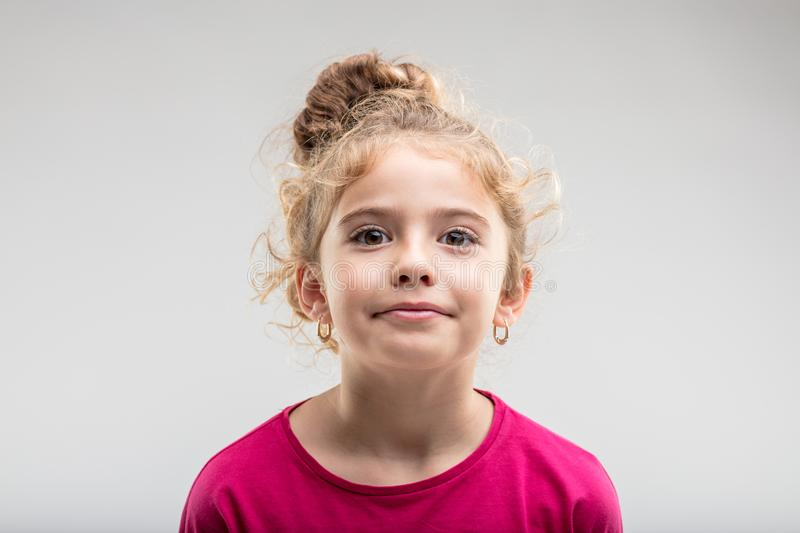 Portrait of young self-assured preteen girl. Looking at camera against plain background royalty free stock photos