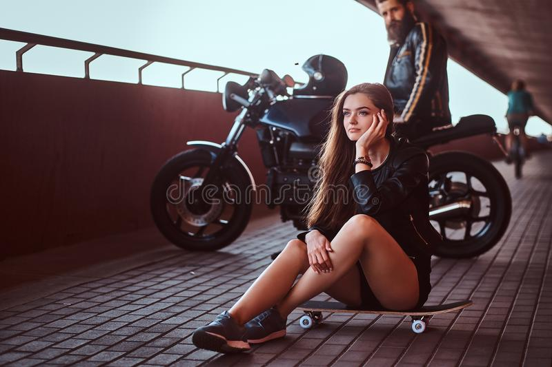 Portrait of a young sensual brunette girl sitting on a skateboard and brutal bearded biker in black leather jacket stock photos