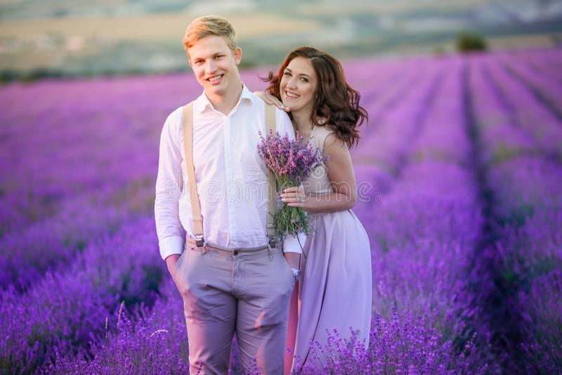 Portrait of young sensual loving couple in a lavender field at sunset. Provence, France stock photo