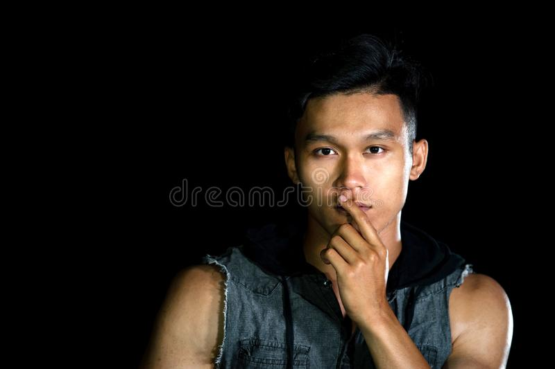 Portrait of young serious handsome boy with muscle on the black background royalty free stock photography