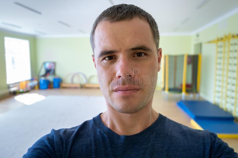 Portrait of a young serious man inside a sports gym royalty free stock image