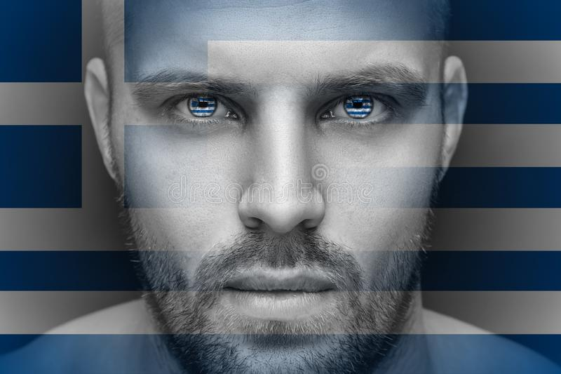 A portrait of a young serious man, in whose eyes are reflected the national flags stock photography