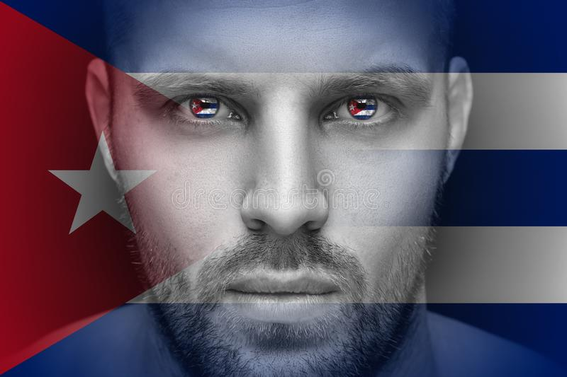 A portrait of a young serious man, in whose eyes is reflected the national flag royalty free stock photography