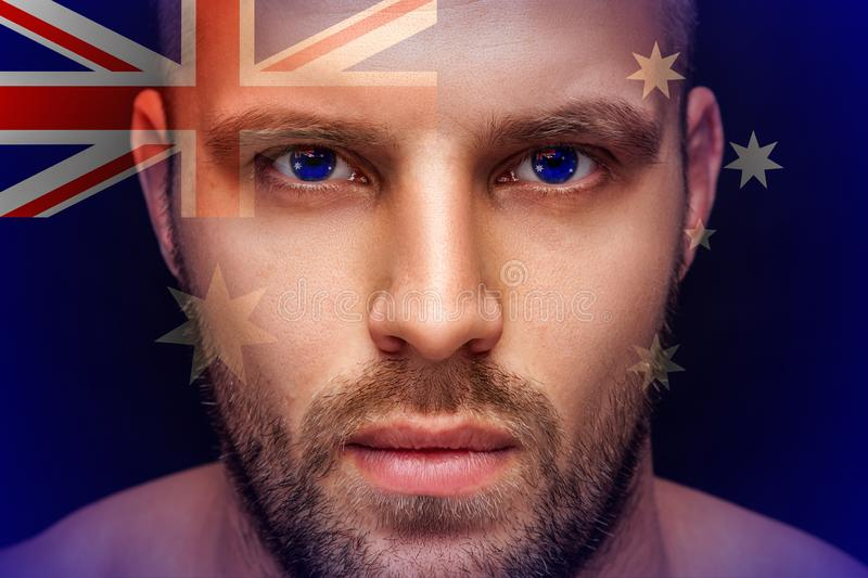 A portrait of a young serious man, in whose eyes are reflected the national flags royalty free stock photography