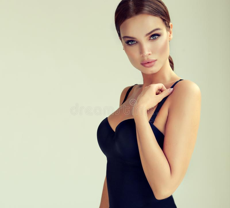 Portrait of young, sexual woman dressed in seductive black body. Makeup and cosmetology. royalty free stock images