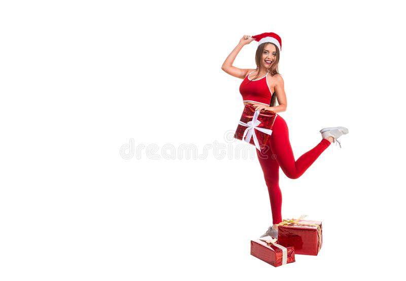 Portrait of young, sexy and beautiful woman in sport suit and Santa hat. White background. Christmas, xmas, x-mas gifts stock images
