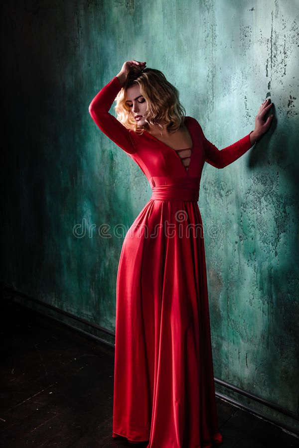 Portrait of young blonde woman in a red dress stock photography