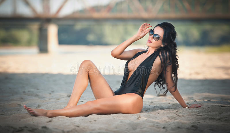 Portrait of young brunette girl in black low-cut swimsuit lying on the beach with a bridge in background. Sensual woman royalty free stock images