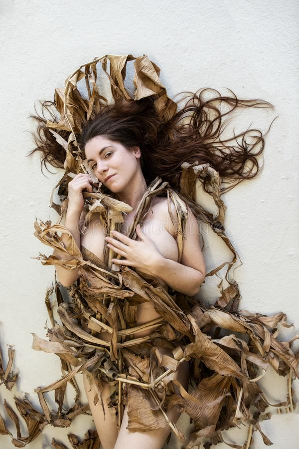 Portrait of a young sexy woman with dark hair artfully covered with dry, withered banana tree lying on the studio floor stock photography
