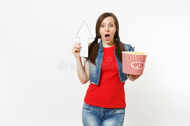 Portrait of young shocked woman in casual clothes watching movie film, holding bucket of popcorn, pointing white arrow. Up on copyspace isolated on white royalty free stock photos