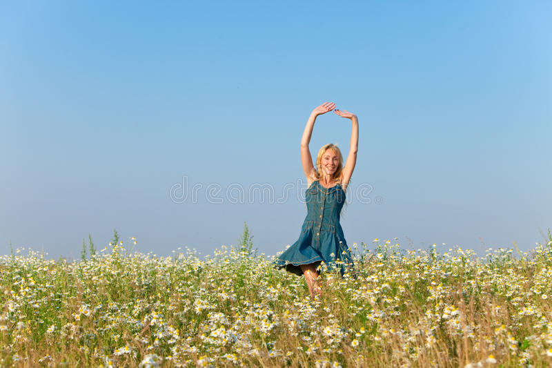 Portrait of the young slender woman in blue jeans a sundress in the field of camomiles stock photo