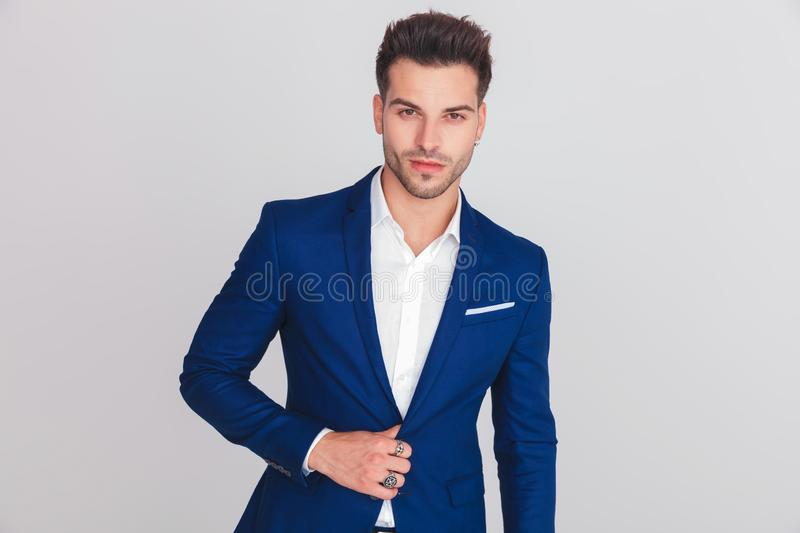 Portrait of young smart casual man buttoning his blue suit. While standing on light grey background stock photography