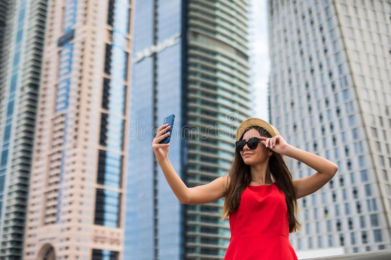 Portrait of young smile woman in red dress, sunglasses and summer hat make selfie or video call on the phone on downtown stock photo
