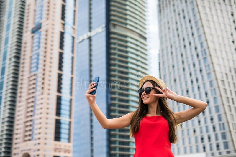 Portrait of young smile woman in red dress, sunglasses and summer hat make video call with victory sign on the phone on downtown stock photography