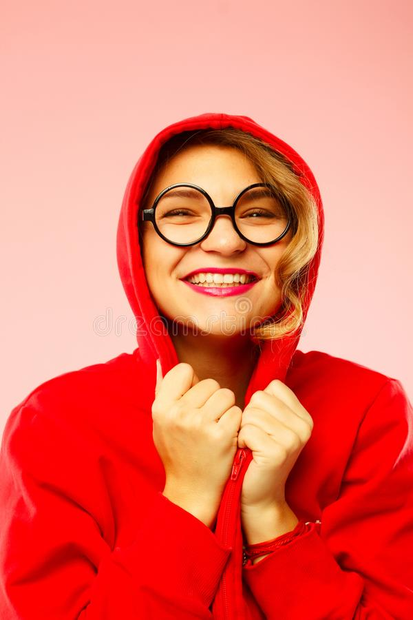 Portrait of young smiley student in black glasses in hood over p royalty free stock photos